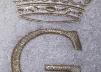 Bordado G con corona sobre jersey