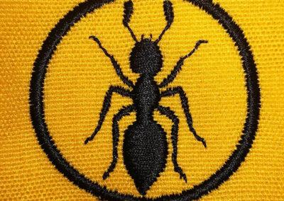 Bordado Hormiga negra en circulo sobre ropa amarilla