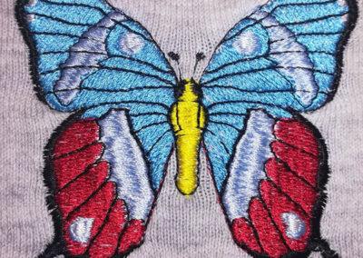Bordado de mariposa multicolor sobre ropa